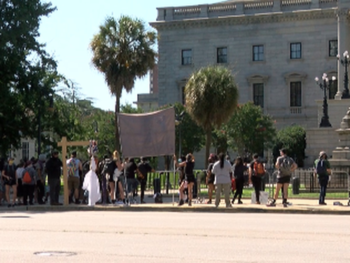 Protestors outnumber pro-Confederate flag organizers during flag raise at the State House