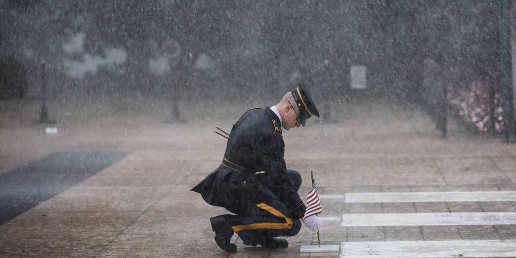 Torrential rain doesn't stop sentinels from placing flags at the Tomb of the Unknown Soldier