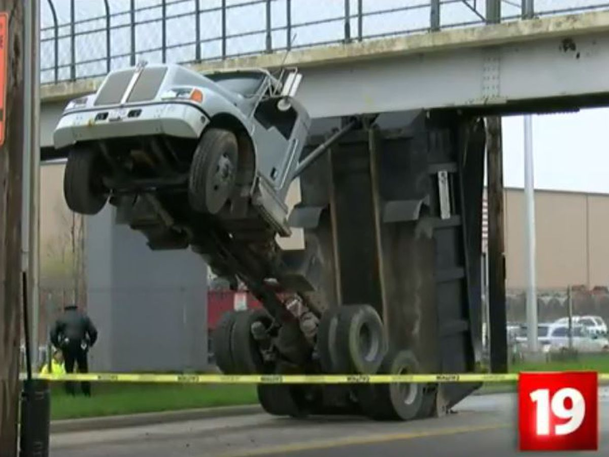 Dump truck removed from under bridge overpass after being stuck for several hours in Cleveland; driver suffers 10 broken ribs (video)